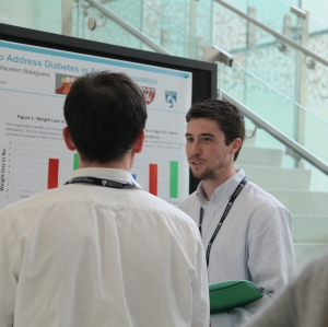 Research assistant, Matthew Manning, explains his project about an intervention to address diabetes in the Latino community during the poster session.