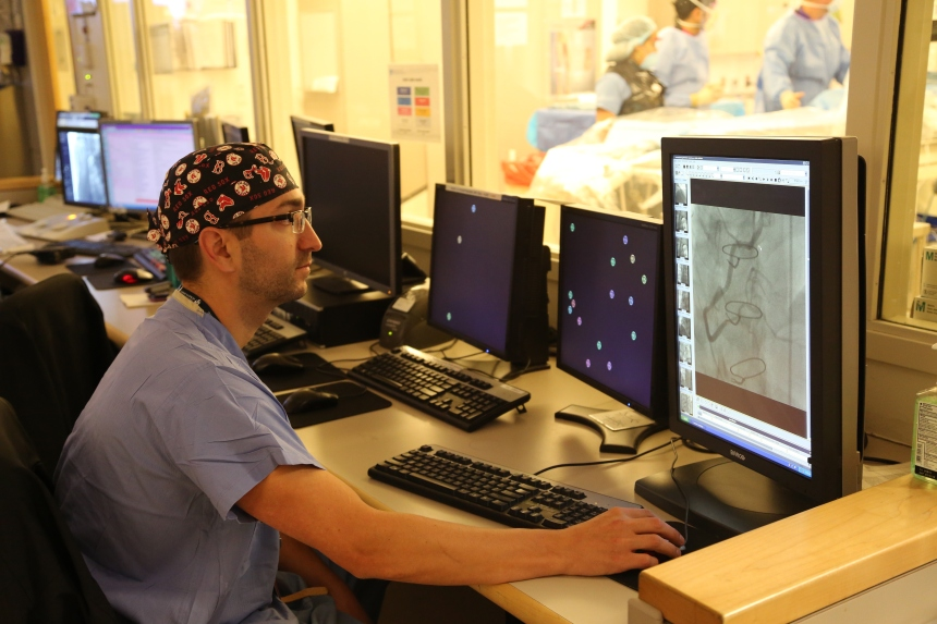 Matt Galvin, PA-C, chief physician assistant in the BWH Cardiac Catheterization Lab, reviews an angiogram film.